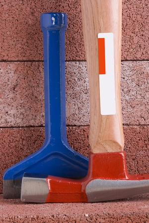 Stonemason's hammer and chisel on a background of red bricks. Banque d'images
