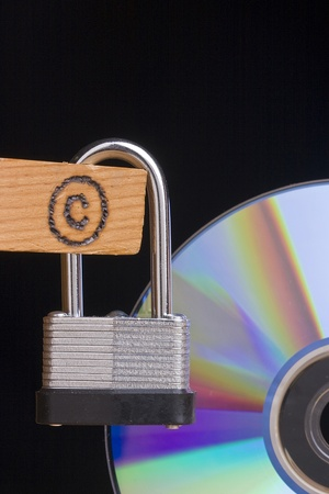 lock symbol: Copyright symbol on a piece of wood attached to a lock next to a CD.