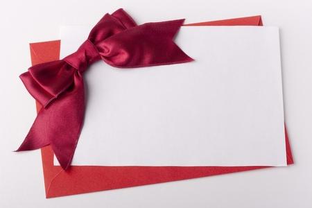 Felicitatie brief met een rode envelop en een scharlaken lint.