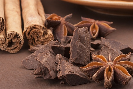 Bitter chocolate in pieces on a brown background with spices.