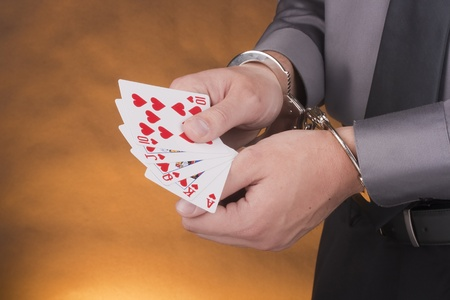 manacle: Arrest card sharper, her hands handcuffed in one hand a set of cards in one suit.