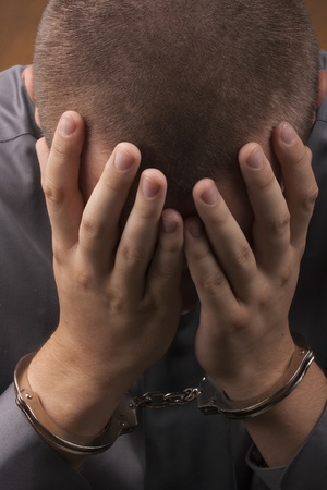 seizure: Arrested in handcuffs covered his face with his hands. Stock Photo