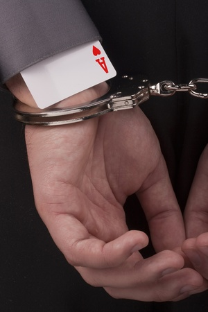 arrestment: In the card tricksters hands handcuffed behind his back.
