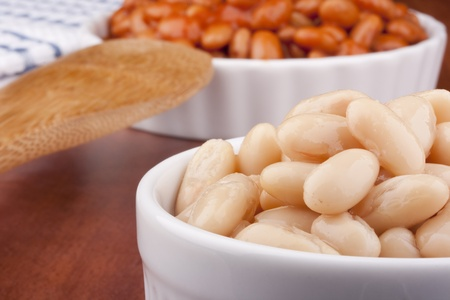 pinto beans: White canned beans in a white ceramic dish with red sauce.