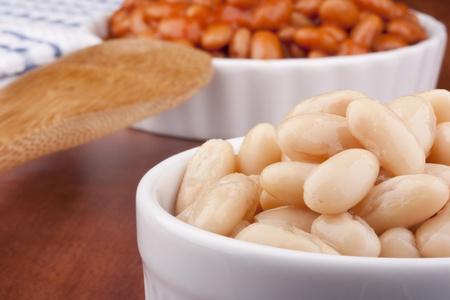 White ingeblikte bonen in een witte ceramische schotel met rode saus. Stockfoto