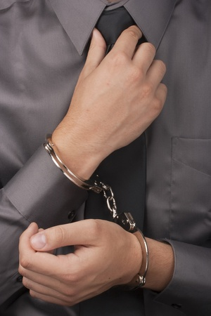 handcuffed: Arrested white man in handcuffs straightens his tie.