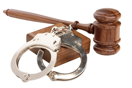 Wooden gavel and handcuffs isolated on a white background. photo