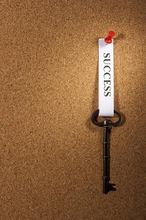 Key with a success tag pinned on a brown board. Add your text to the background.