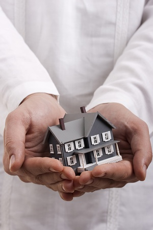 home safety: Man in white holding a model of a house in his hands.