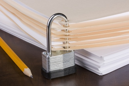 Stack of folders closed by a metal lock. Stock Photo - 8752360