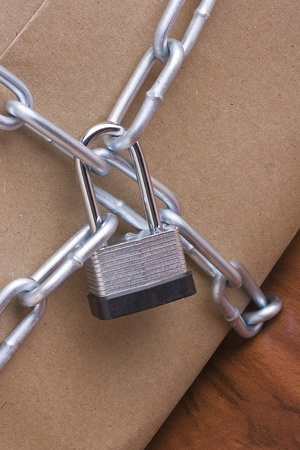 Metal lock and chain on a brown background.