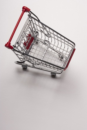 Empty shopping cart with the red handle on a white background. Stock Photo - 8860366