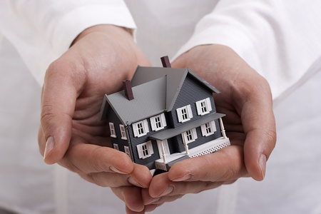 hand holding house: Man in white holding a model of a house in his hands.