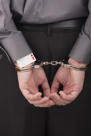 In the card tricksters hands handcuffed behind his back. Stock Photo - 8970141