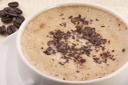 Cappuccino in a white ceramic cup with coffee grains. Stock Photo - 8970145