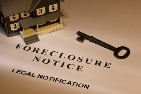 A key laying next to a house model and a foreclosure notice.