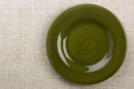 Round ceramic dish on a background mat for the second course. photo