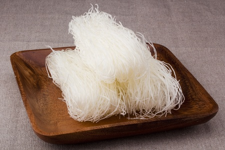 rice noodles: Close-up of white rice noodles on a brown plate.