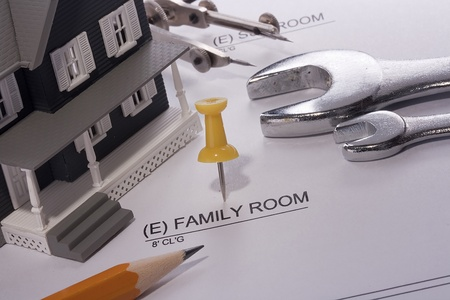 House model and drafting tools on a family room construction plan. photo