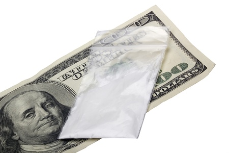 drug trafficking: Small sealed bag with drugs laying on a one hundred dollar bill.