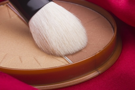 Powder brush and brown powder on a red background. 스톡 콘텐츠