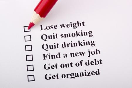 weight loss plan: Una matita rossa posa su una carta con un elenco di obiettivi.