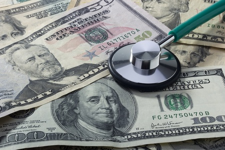 Medical stethoscope laying on various denominations of American money. photo