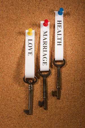 characteristic: Keys with tags pinned on a brown bulletin board.