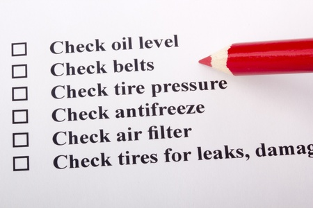 A checklist for vehicle safety with a red pencil. photo
