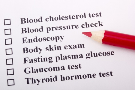 screening: A red pencil laying on a health examination checklist.