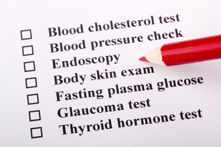 A red pencil laying on a health examination checklist. Stock Photo