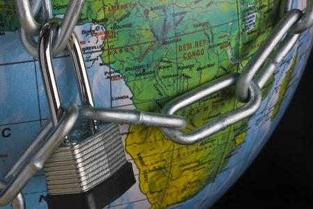 Metal lock and chain on a globe. photo