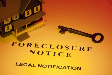 housing problems: A key laying next to a house model and a foreclosure notice.