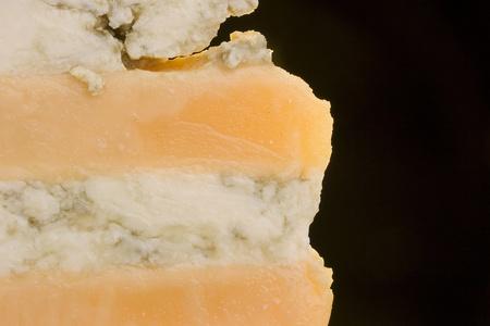 黒い背景に青いチーズ スライスとグロスター チーズ。