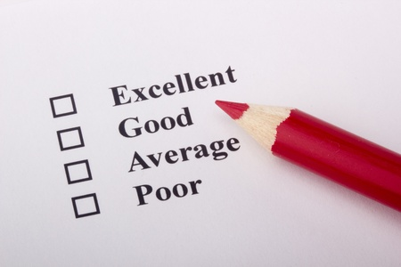 unsatisfied: A red pencil laying on a customer service survey. Stock Photo