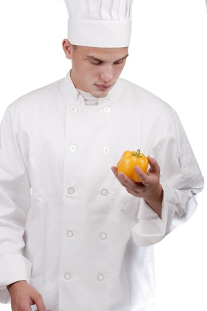 The young chef in uniform and chefs hat holding a yellow pepper.