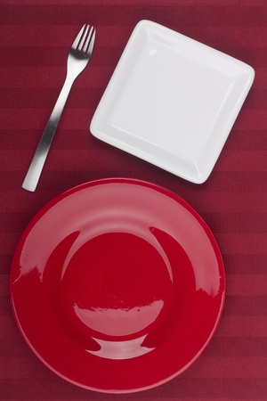 Ceramic plates for table on a red background.