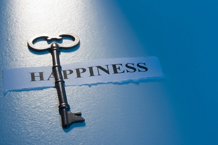 live happy: A key laying on a piece of paper with the word