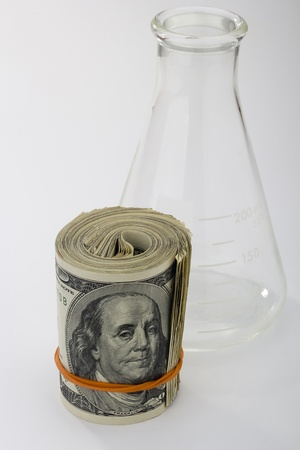 A roll of American money and an erlenmeyer flask on a white background. Stock Photo - 9238933