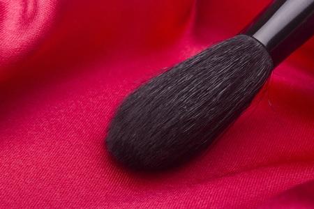 赤い背景の上の化粧品の黒のブラシ。 写真素材