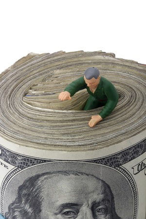 Miniature man getting out of a roll of American money.