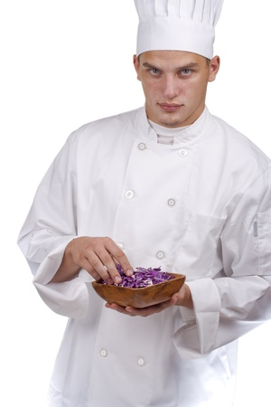 The young chef in uniform and chefs hat in his hands chopped red cabbage.
