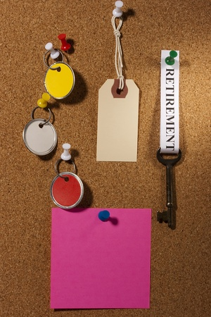 Key with a retirement tag pinned on a brown board. Add your text to the paper. photo