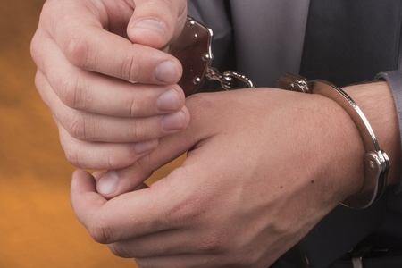 sequestration: Arrest, close-up shot mans hands with handcuffs.
