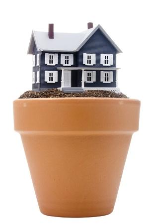 Model of the house on the fertile soil of falling asleep in a ceramic flower pot. Stok Fotoğraf