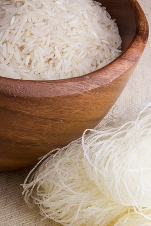 rice noodles: Close-up of white rice in a brown plate and rice sticks.