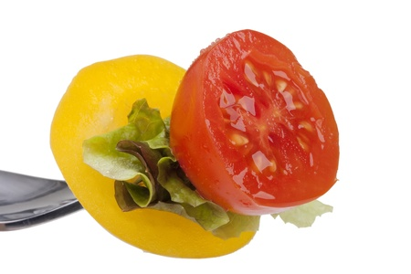 Sandwich of tomato, peppers and lettuce on a fork.