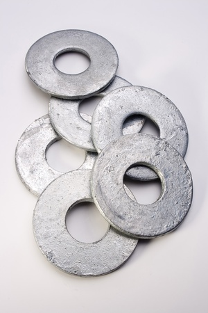 Pile of flat silver washers on a white background.