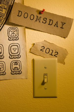 Old papers with the words Doomsday and 2012 and a Mayan calendar next to a light switch representing the end of the world. photo