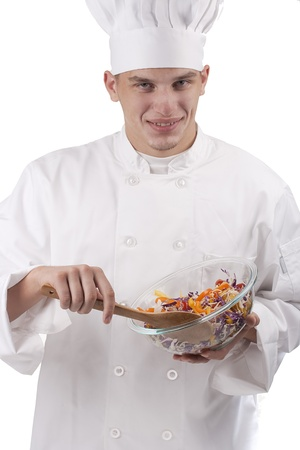 The young chef in uniform and chefs hat in the bowl of salad mixes. Banco de Imagens